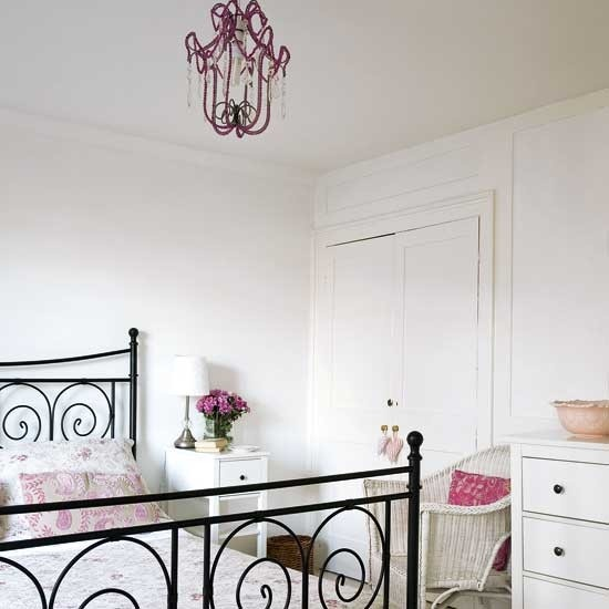 a beautiful feminine bedroom with a black metal bed, a purple crystal chandelier, touches of pink and lilac and some printed bedding