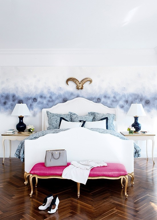 a contemporary feminine bedroom with a catchy accent wall, refined furniture, touches of gold, a pink bench and printed blue bedding
