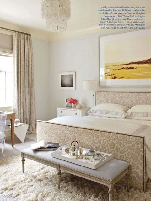a neutral and refined feminine bedroom with printed textiles, a fluffy rug and a chic chandelier and a bench