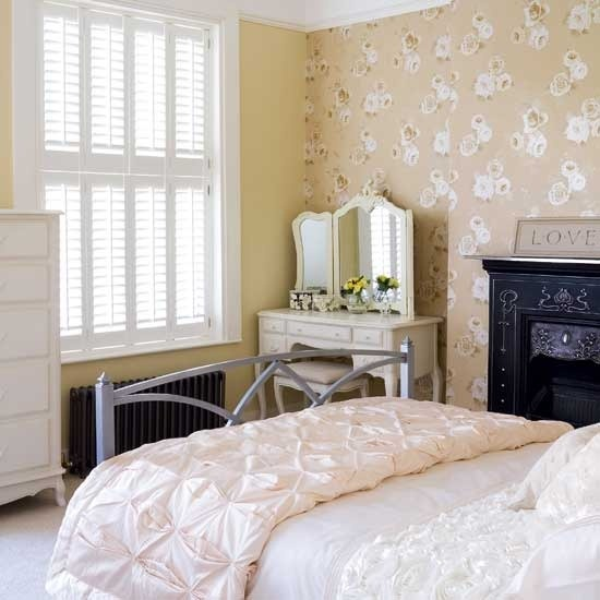 a neutral feminine bedroom with floral wallpaper walls, elegant and chic furniture, a non-working fireplace and a beautiful vanity with a mirror