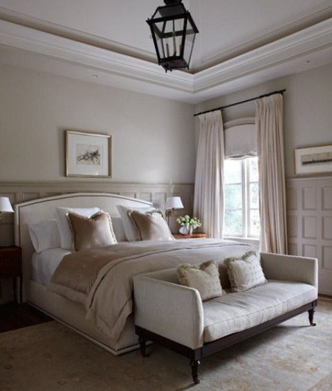 a chic neutral bedroom with paneled walls, elegant furniture, some artworks and a statement lantern over the space, shiny bedding and pillows