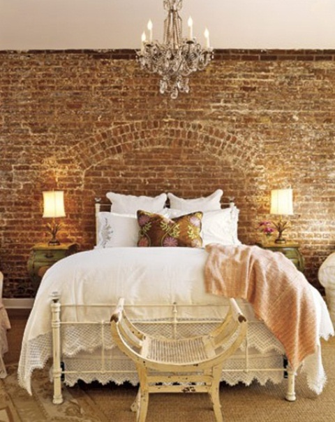 a refined girlish bedroom with an exposed brick wall, elegant white furniture, white and floral bedding and a beautiful crystal chandelier