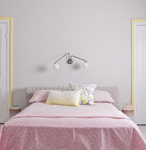 a modern feminine bedroom with grey walls, a grey upholstered bed, pink and yellow bedding and yellow frames around the doors