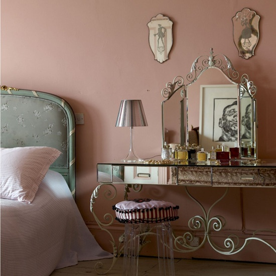 a pink French-style boudoir bedroom with a blue floral bed, elegant vanity and a stool and some antique mirrors is lovely