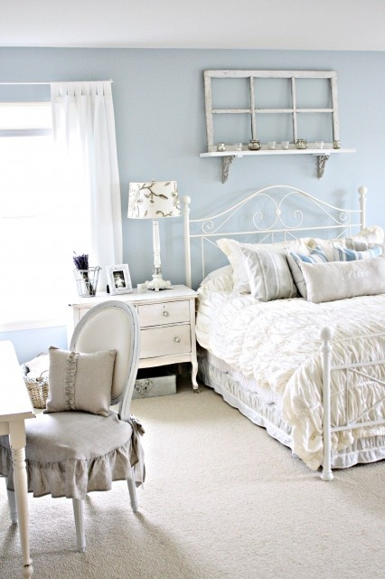 a shabby chic feminine bedroom with powder blue walls, vintage furniture in white, neutral and printed linens and a ruffled chair
