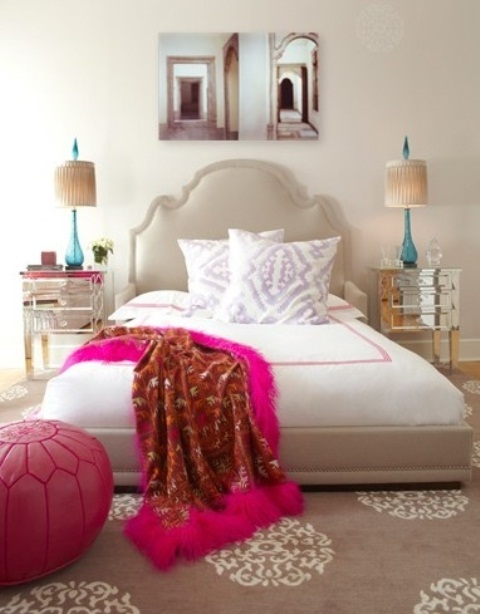 a bold feminine bedroom with a grey upholstered bed, mirrored nightstands, bold fuchsia touches and pretty artworks over the bed