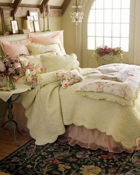 a romantic shabby chic bedroom with neutral walls, a neutral bed with floral and pink bedding, pretty artworks and a crystal chandelier plus a refined nightstand