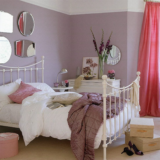a feminine bedroom with lilac walls, a white forged bed, pink curtains, a gallery wall of mirrors and some artworks and blooms