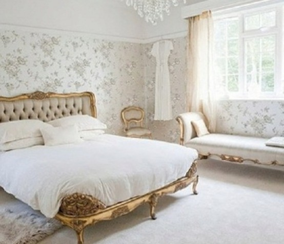 a neutral feminine bedroom with floral wallpaper walls, exquisite furniture with gold touches and a crystal chandelier