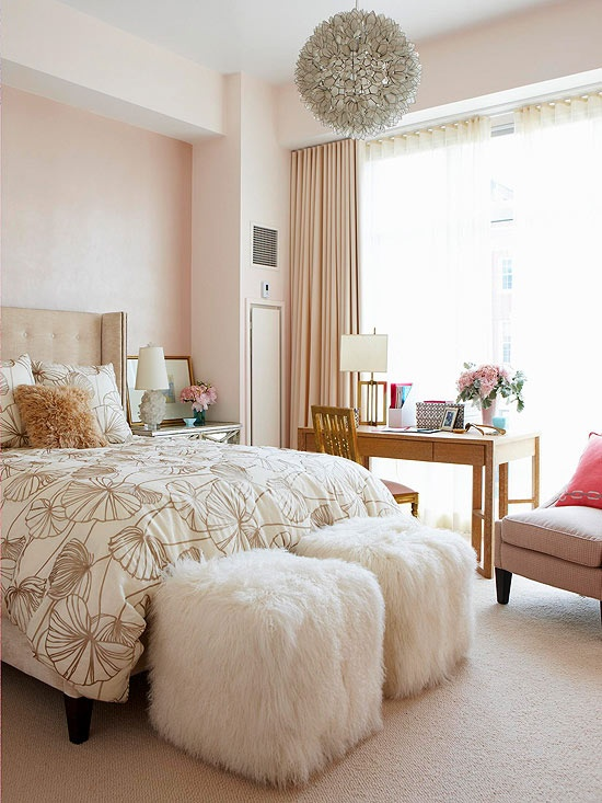 a pretty pink bedroom with a neutral bed, white fur stools, a simple table and a chair, a floral chandelier and pink curtains