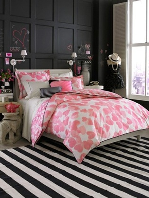 a bold feminine bedroom with a black paneled wall, neutral furniture, bright heart printed bedding, a striped rug and some more heart decor