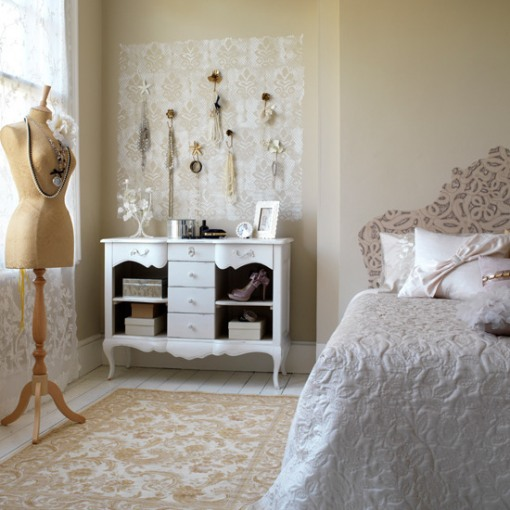 a neutral vintage bedroom with warm-colored walls, a pretty patterned bed, a dresser with accessories and a mannequin as decor is very Parisian-style