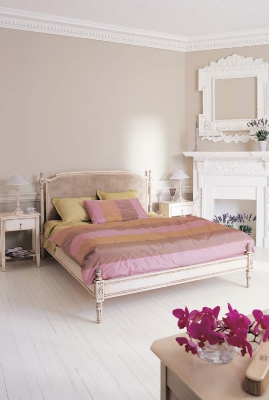 a vintage-inspired feminine bedroom with grey walls, a carved wooden bed, a faux fireplace, picture frames and blooms