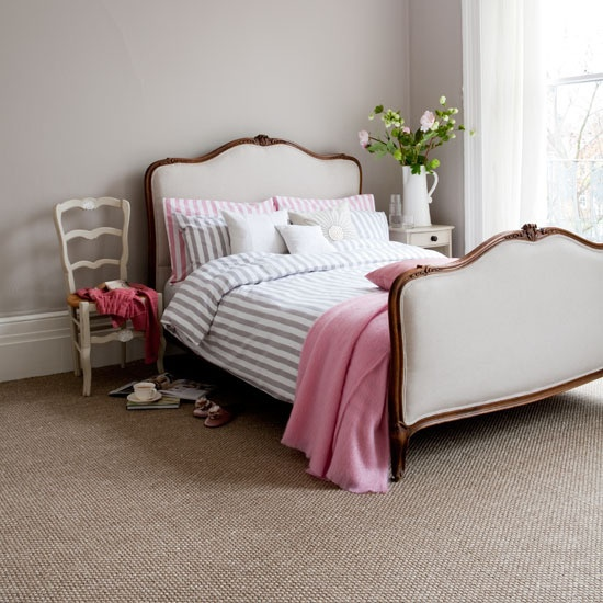 a laconic and romantic feminine bedroom with a refined white bed, striped and pink bedding, a chic chair and some pink blooms and greenery is lovely