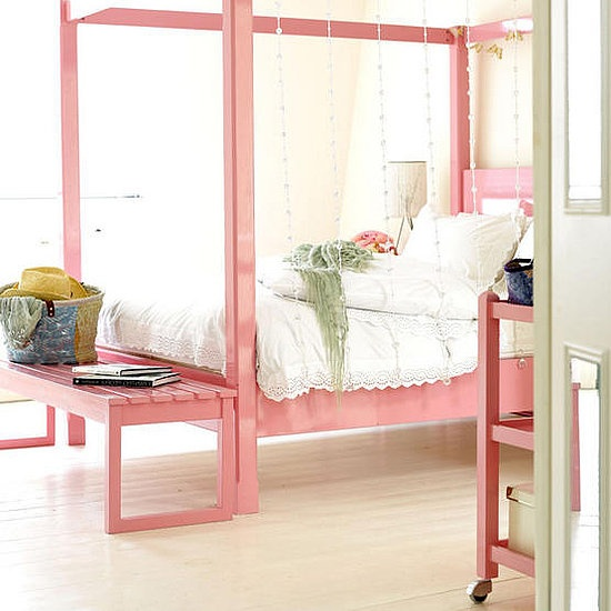 an airy feminine bedroom with a pink canopy bed and a bench, a pink console table and crystals plus simple bedding