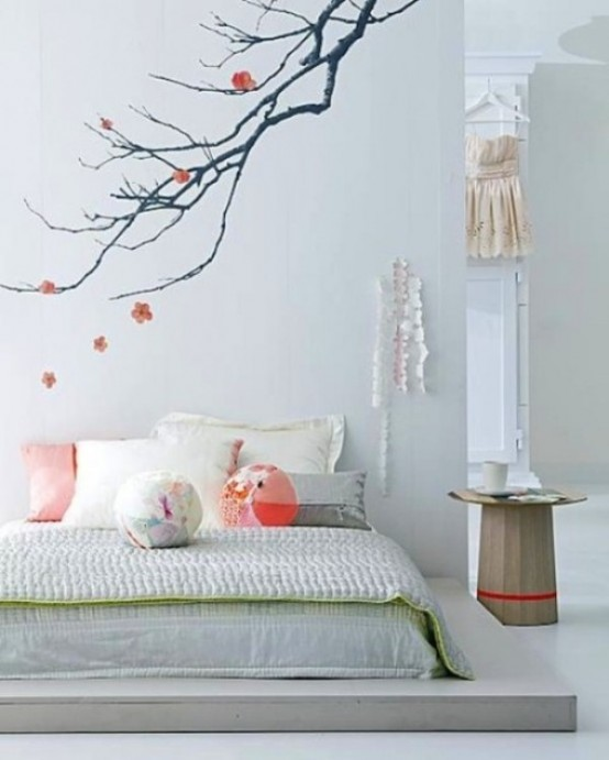 an airy and light Japanese-inspired bedroom with a platform bed, some Asian furniture and a sakura branch decal on the wall