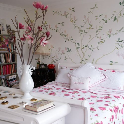 an ethereal feminine bedroom with a painted floral wall, simple yet catchy furniture, bright floral bedding and bold pink blooms on branches
