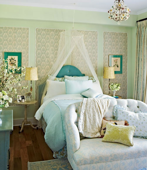 a refined feminine bedroom paneled walls, a blue upholstered bed and dresser, a floral loveseat and a florla chandelier is very refined and cool