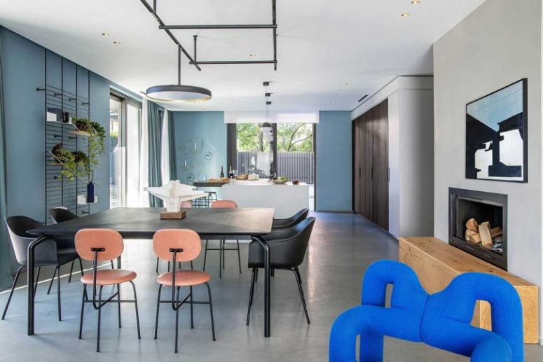 The main layout is an open space with a kitchen, dining room and a living room, with blue walls and catchy pendant lamps