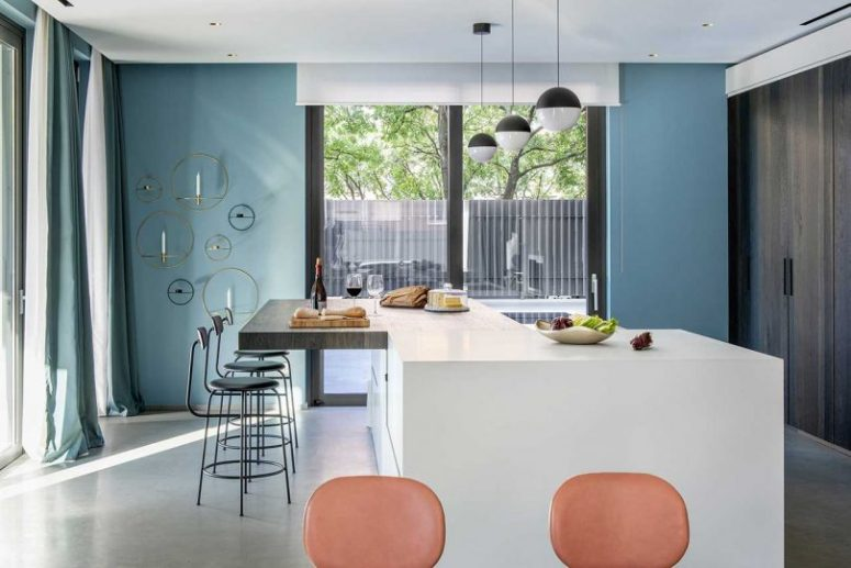 The kitchen is done with dark wooden storage units instead of traditional cabinets, and a large kitchen island with a bar zone