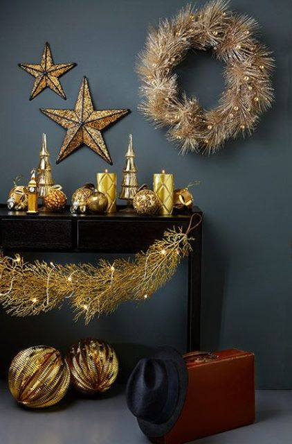 A Black Console Table With Oversized Gold Balls, Gold Patterned Candles, A Gold Wreath And Stars Plus Lights Is Amazing For The Holidays