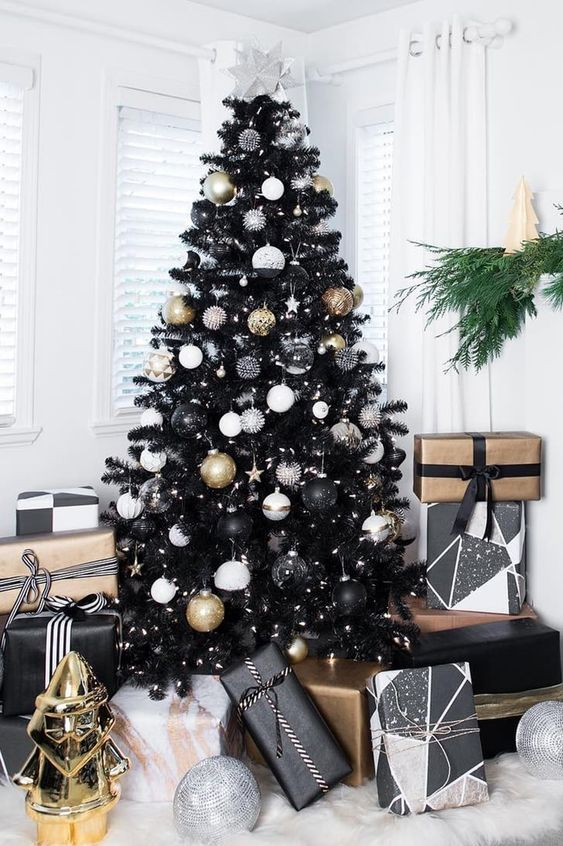 A Classy Christmas Tree In Black With White, Black And Gold Ornaments And Stars And Lights Is All Glam And Chic