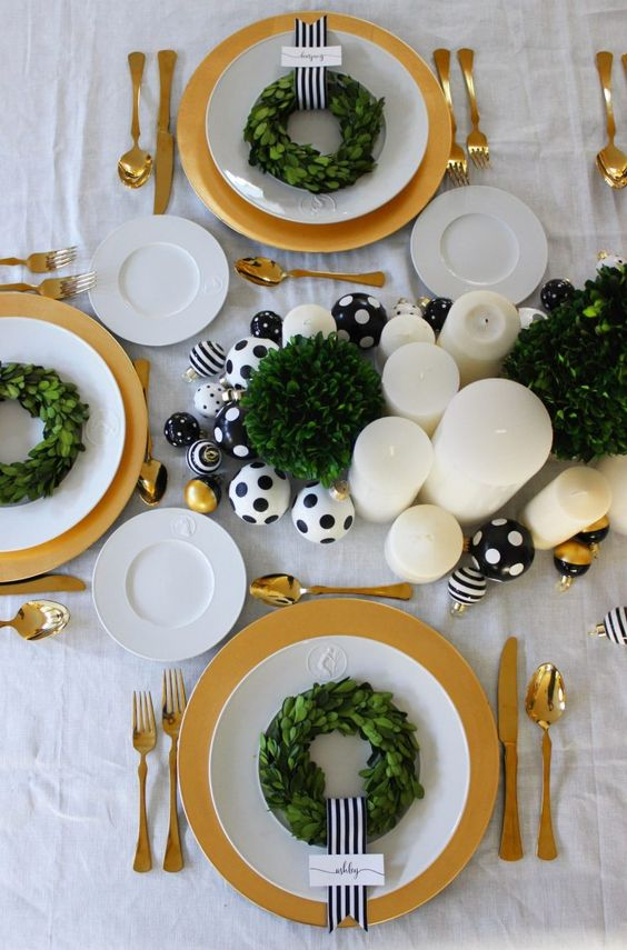 A Chic And Glam Christmas Tablescape With Black And White Polka Dot Ornaments, Pillar Candles And Greenery Wreaths Plus Gold Cutlery And Chargers