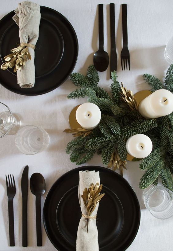 A Modern And Stylish Christmas Tablescape With Black Plates And Chargers, Black Cutlery, Gold Foliage And Candleholders And Fir Branches