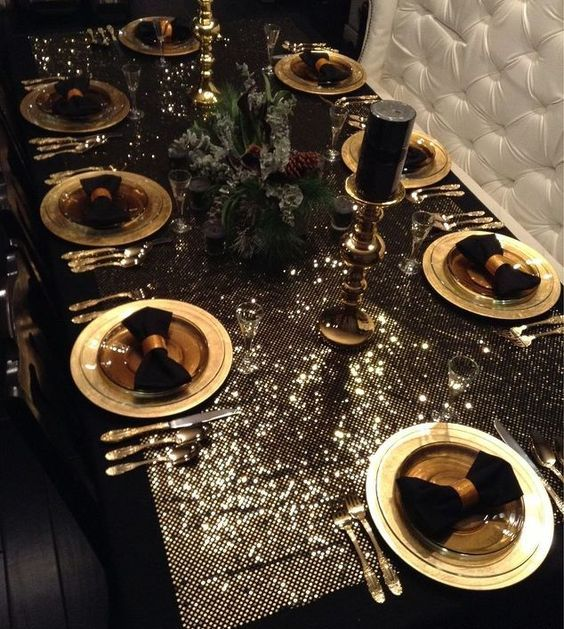 A Luxurious Glam Christmas Tablescape With A Shiny Tablecloth, Gold Chargers And Cutlery, Black Napkins And Candles And A Fir And Pinecone Centerpiece