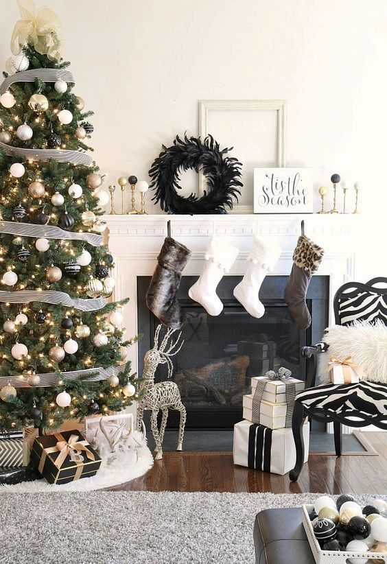 A Stylish Black, Gold And White Christmas Tree With Lights, Striped Ribbons And A Tulle Bow On Top Is Lovely