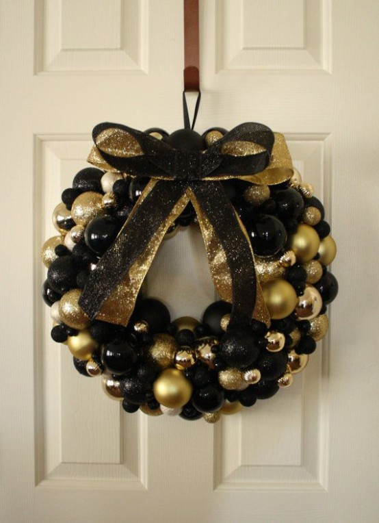 A Black And Gold Christmas Wreath Made Of Ornaments And Topped With A Black And Gold Bow To Make It More Glam And Chic Is Ideal For Indoors And Outdoors
