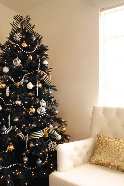 A Chic And Refined Black Christmas Tree With Lights, Black, Gold And White Ornaments And Snowflakes And Beads