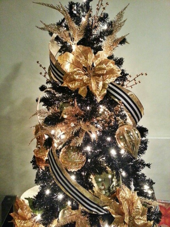 A Gold And Black Christmas Tree With Striped Ribbons, Shiny Touches And Ornaments, Lights And Twigs Is Lovely And Cool
