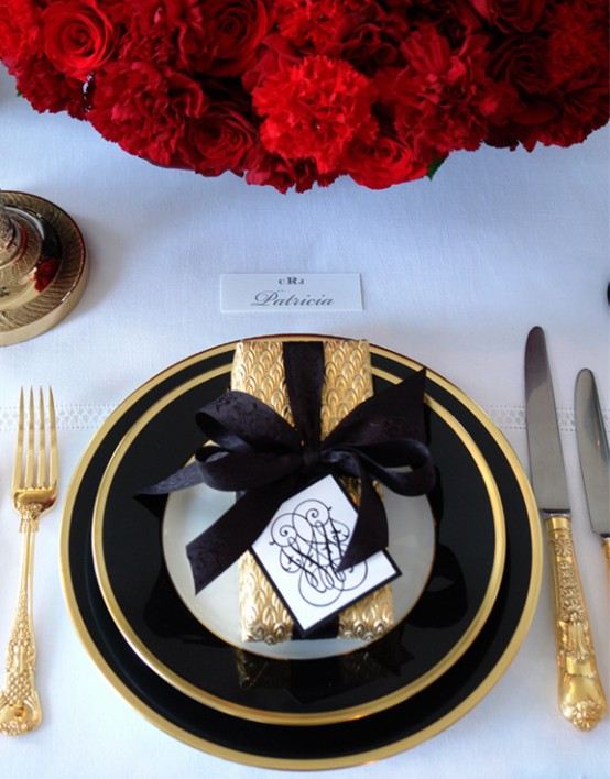 A Super Elegant And Refined Christmas Or Nye Table With Black And Gold Porcelain, Cutlery And A Gift Box Plus Red Roses Is Wow