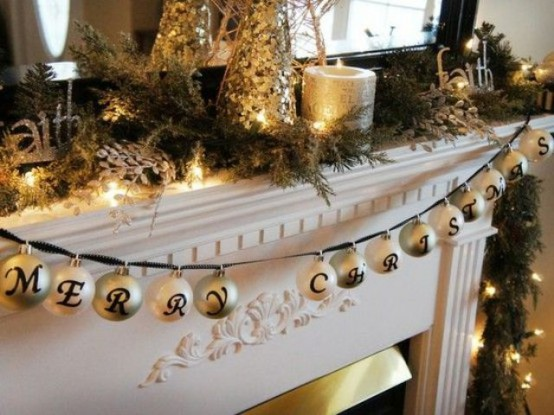 A Christmas Mantel Decorated With Fir Branches, Gold Candles, Mini Trees And A Galrand With Ornaments And Letters Is Very Lovely