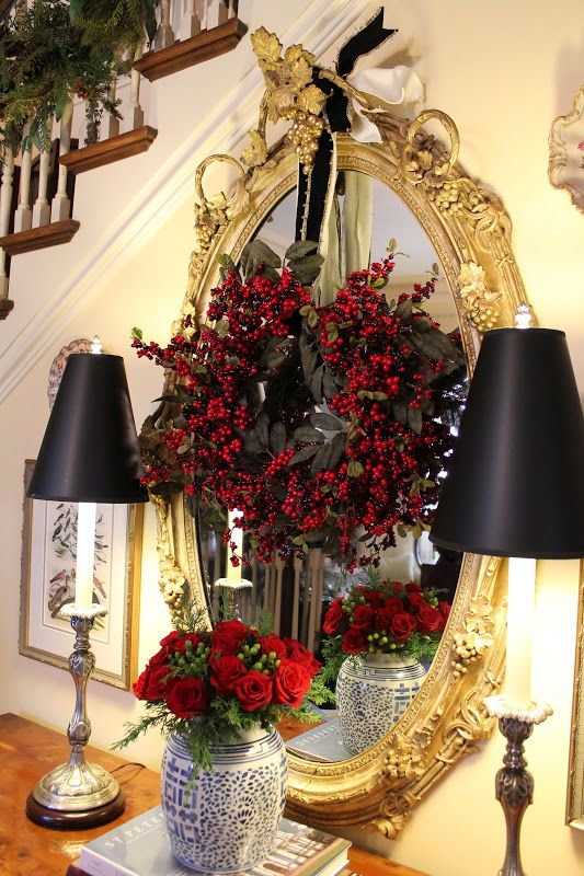 A Mirror In A Refined Gold Frame With A Black Foliage And Red Berry Wreath And Black Lamps Is Pure Elegance And Chic