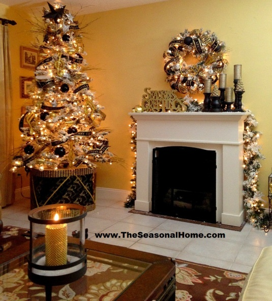 Elegant Black And Gold Holiday Decor With A Pretty Flocked Christmas Tree Decorated With Lights, Ribbons And Black And Gold Ornaments And A Mantel With A Matching Wreath And Gold Candles In Black Candleholders