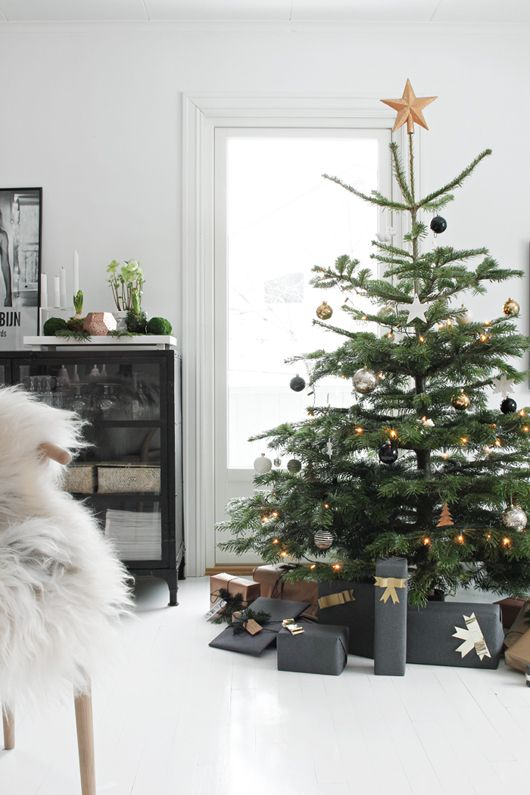 A Christmas Tree With Black, Silver And Gold Ornaments And Gold Star Topper And Lights Is Modern And Chic Elegance
