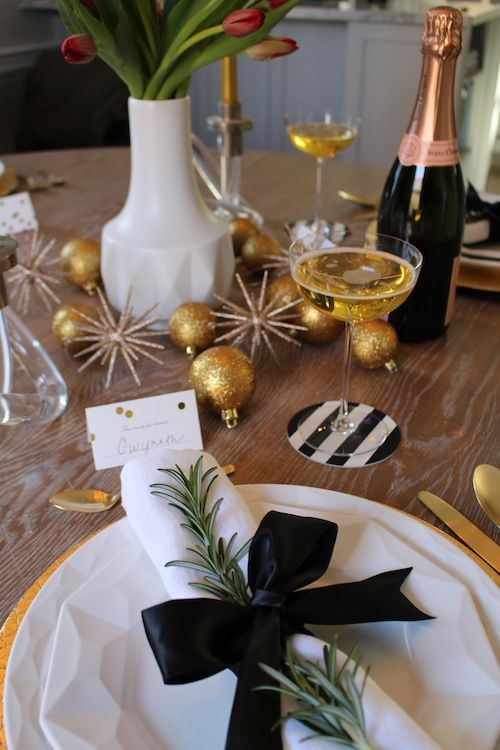 A Black And Gold Christmas Table With Snowflakes And Balls With Glitter, Gold Chargers And Cutlery And Black And White Touches