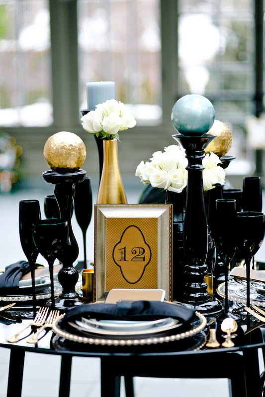 An Art Deco Christmas Or Nye Tablescape With A Black Table, Glasses, Plates, Chargers, Black Stands With Large Spheres Is Wow