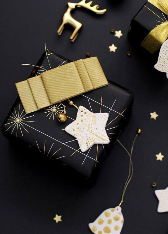A Black Christmas Gift Wrapped With A Gold Bow, A Clay Star Ornament And Smaller Gold Ones Is Lovely And Very Chic