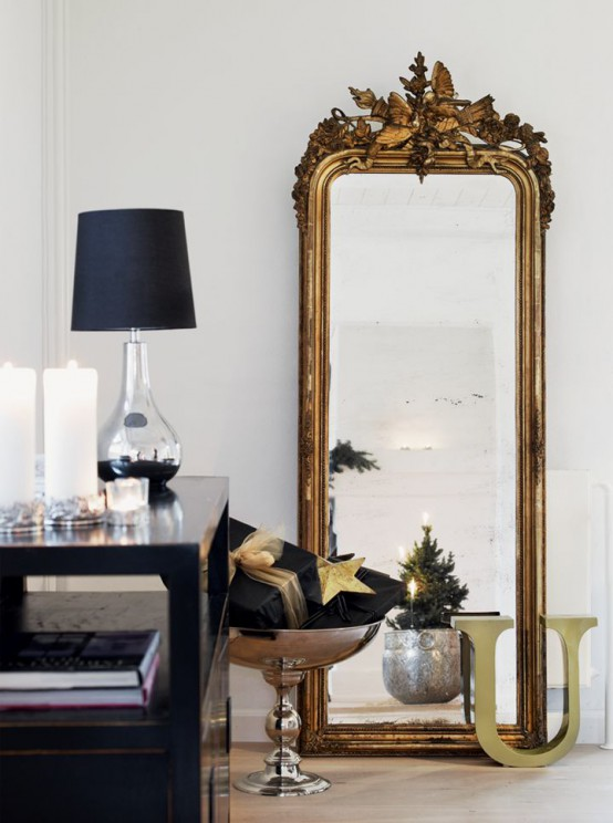 A Full Height Mirror In A Refined Gilded Frame And A Stack Of Black And Gold Christmas Gifts And A Table Lamp For Lovely And Chic Decor