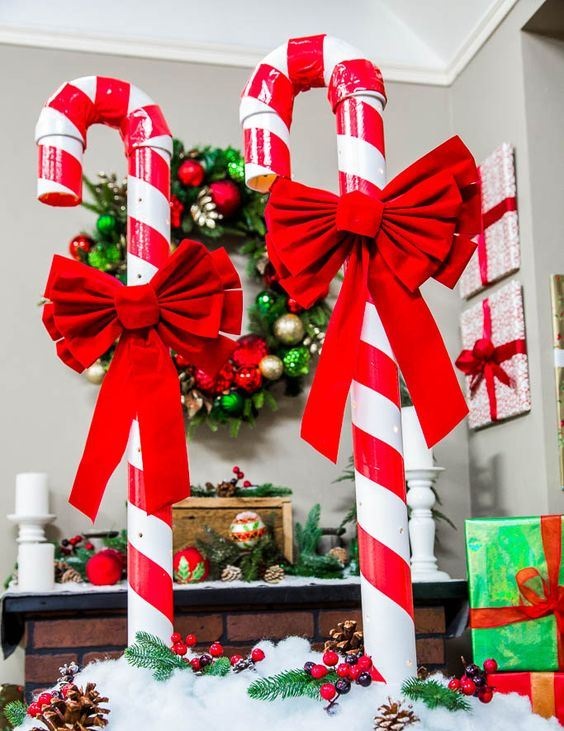 a bright Christmas decoration of candy canes with red bows, faux snow, berries and pinecones is amazing and easy to recreate