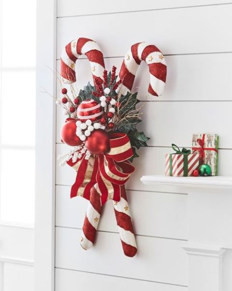 a bright Christmas decoration of oversized candy canes, foliage, berries, bright red and white ornaments and a large bow is lovely