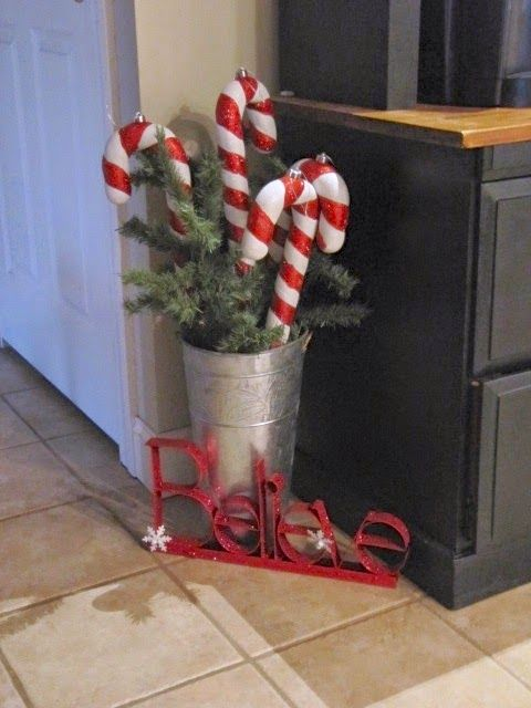 classy Christmas decor with a bucket with fir branches, candy canes and letters is gorgeous and whimsical
