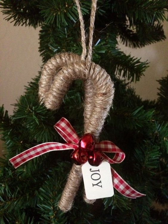 a cozy rustic Christmas ornament - a twine wrapped candy cane with red bells and a plaid bow is a lovely idea
