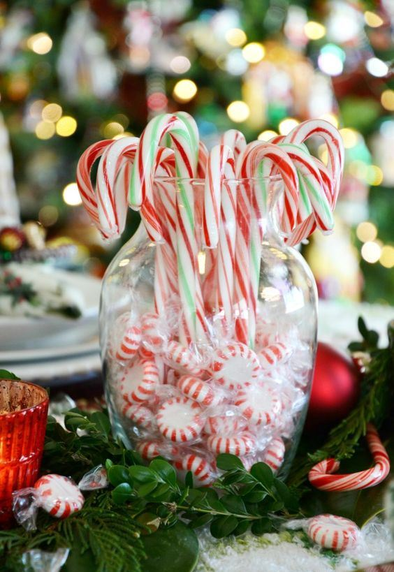 a simple edible decoration of a vase with peppermints and candy canes and greenery around is a stylish idea for holiday decor
