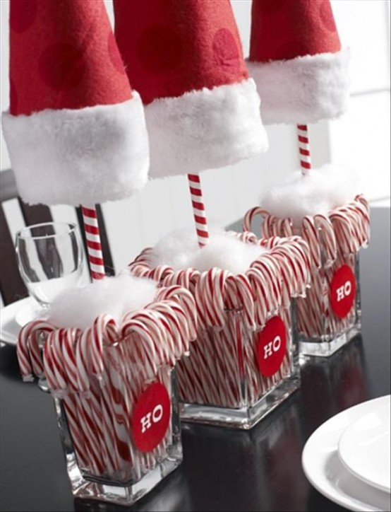 bold and pretty Christmas decor of vases with candy canes, faux snow and large Santa hats is a very fun and whimsical idea to rock