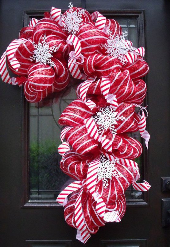 a red and white candy cane shaped wreath made of ribbons and snowflakes is a very creative and cool decoration for Christmas