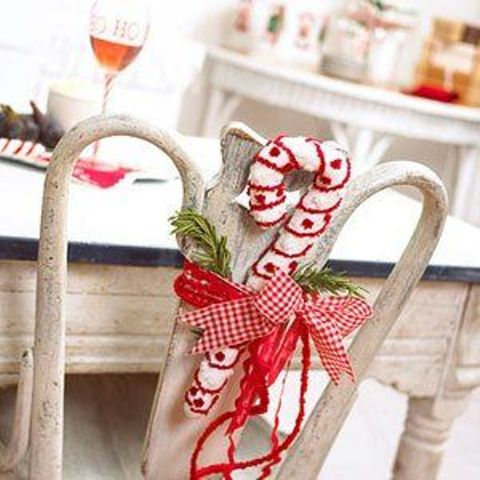 a vintage chair decorated with a knit candy cane and a red bow plus some fir branches is a lovely and cool idea for Christmas